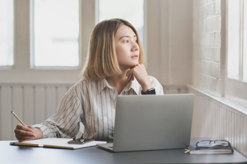mulher reflexiva enquanto trabalha olhando para a janela