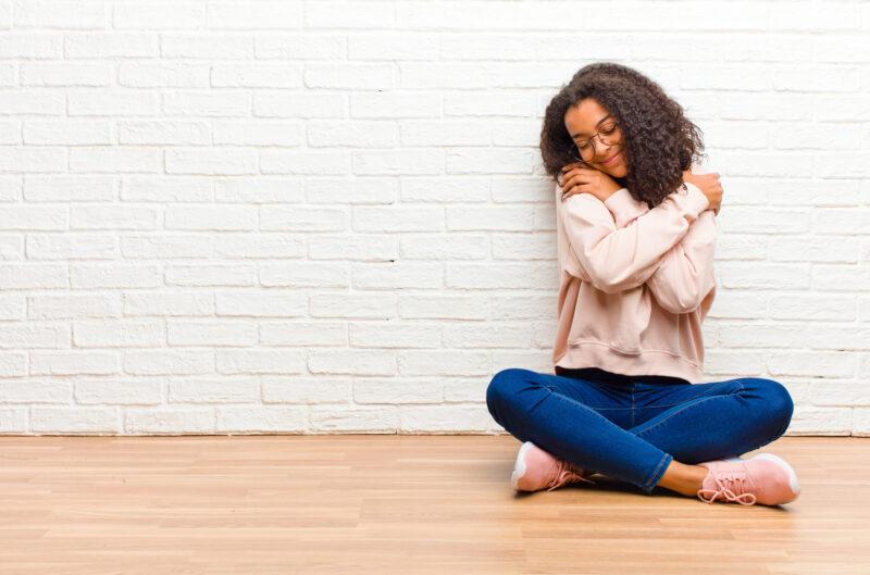 mulher sentada no chão abraçando a si mesma